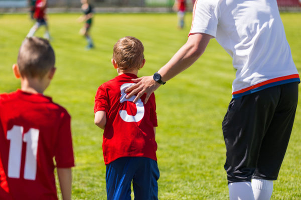 Youth Soccer Substitution. Junior Soccer Football Team Change. Coach Motivating Young Soccer Player. Coaching Children School Soccer Team